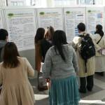 (5) 来場者に説明する学生たち。こちらにも学長先生が!すべての班の発表を丁寧に聞いてくださいました。